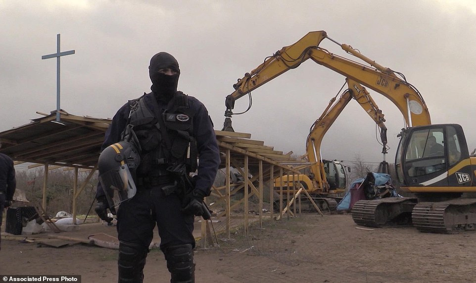 In this frame grab from APTN taken on Monday Feb. 1, 2016, a policeman stands guard as a mechanical digger destroys a makeshift church at a migrant camp in Calais, France. A regional official said the operation Monday was the culmination of a two-week effort to clear a 100-meter security zone around the perimeter of the camp. The official said authorities the migrants and charity groups helping them were informed Jan. 19 of the pending demolition, and that no one was hurt in the operation. (AP Photo/APTN)