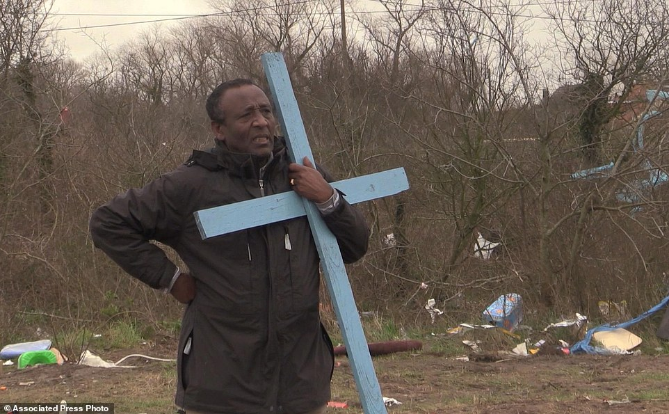 In this frame grab from APTN taken on Monday Feb. 1, 2016, Reverend Teferi Shuremo holds a cross and watches as a makeshift church is destroyed at a migrant camp in Calais, France. A regional official said the operation Monday was the culmination of a two-week effort to clear a 100-meter security zone around the perimeter of the camp. The official said authorities the migrants and charity groups helping them were informed Jan. 19 of the pending demolition, and that no one was hurt in the operation. (AP Photo/APTN)