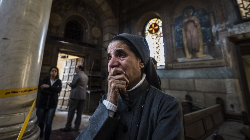 A nun reacts as Egyptian security forces (unseen) inspect the scene of a bomb explosion at the Saint Peter and Saint Paul Coptic Orthodox Church on December 11, 2016, in Cairo's Abbasiya neighbourhood. The blast killed at least 25 worshippers during Sunday mass inside the Cairo church near the seat of the Coptic pope who heads Egypt's Christian minority, state media said. / AFP PHOTO / KHALED DESOUKI
